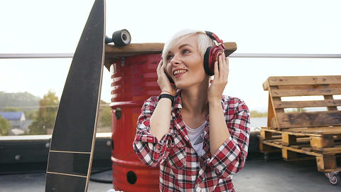 Cute blonde girl in red headphones listening to music and dancing. Young hipster Footage