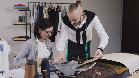 Two people multi-ethnic fashion designers working with patterns and fabrics at Footage