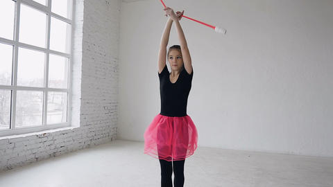 Sport and success. Woman gymnast in black sportssbody and pink skirt with pink Footage