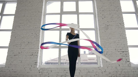 Bottom view. Flexible gymnast dressed in black body with colored tape in his Live Action