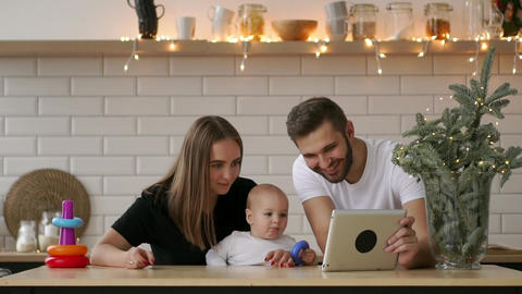 Parents with baby boy playing with digital tablet Footage