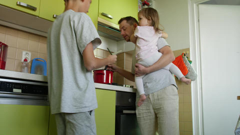 Cooking father holding girl in arms lauds son for homework ビデオ