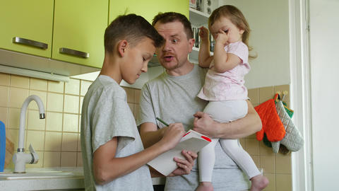 Father with daughter in hands yells at son for homework in kitchen ビデオ