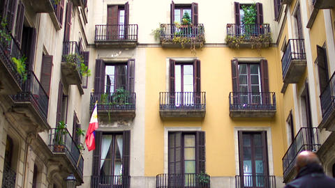 Traditional building facade, Spanish architecture, people walking on street Live Action