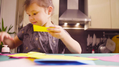 Little girl cutting colored paper with scissors Footage