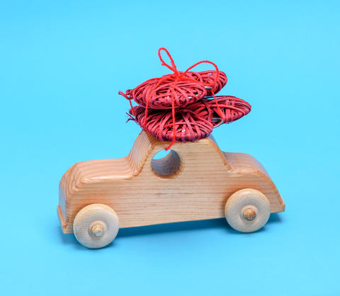 small wooden children's car carries a wicker red heart Photo