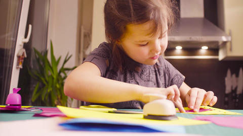 Little girl glueing and cutting colored paper Footage