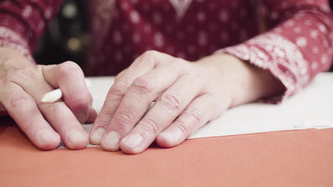 Female hands drawing outline of a paper pattern with a pencil Footage