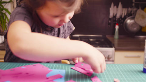 Little girl glueing colored paper Footage