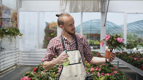 A young guy is a gardener in mittens and a garden apron, smiling and look on the Live Action