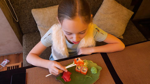 Top view girl eating sushi roll with chopsticks in japanese sushi restaurant Live Action