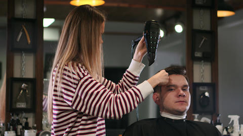 Barber drying male hair in hairdressing salon. Close up hairdresser blowing man Footage