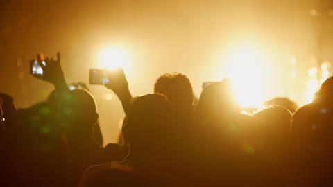 Fans taking video and photos on smart phone at concert strobing flashing lights Footage