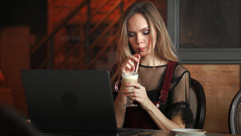 Focused attentive woman in headphones sits at desk with laptop, looks at screen Live Action