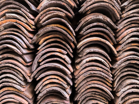 Background of columns of clay tiles stacked in a pile, for roof construction フォト