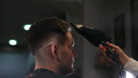 Male hairstyle in salon. Man hair drying in barber shop. Barber styling hair Live Action