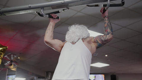 Santa Claus in the gym pulls himself up on the horizontal bar Footage