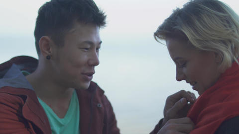 Date of interracial couple outdoors. Asian guy kisses his... Stock Video Footage