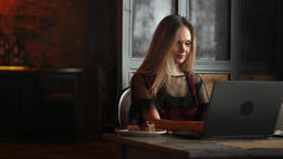 Focused attentive woman in headphones sits at desk with laptop, looks at screen Footage