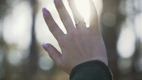 Female hand is played with the sun. Girl looks at the sun through her hand Live Action