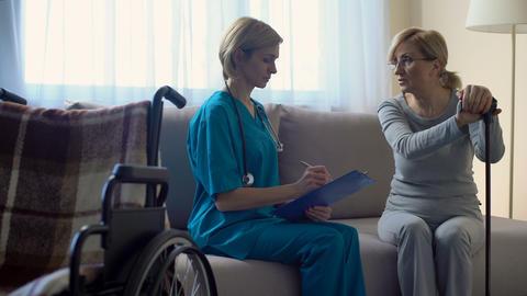 Female doctor talking to senior woman at hospital, making notes, rehabilitation Footage