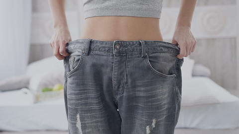 A beautiful, skinny girl demonstrates her old, too big gray trousers on the Live Action