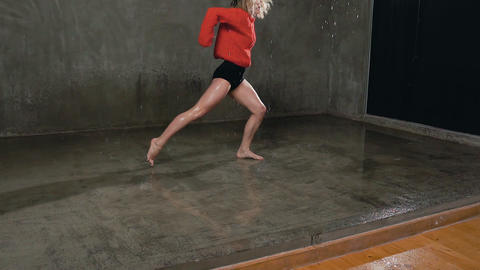 A professional dancer performs a modern dance under the water rain on stage in Live Action