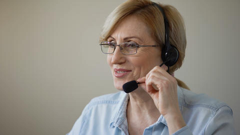 Attractive woman with headset consulting clients of travel agency, services Live Action