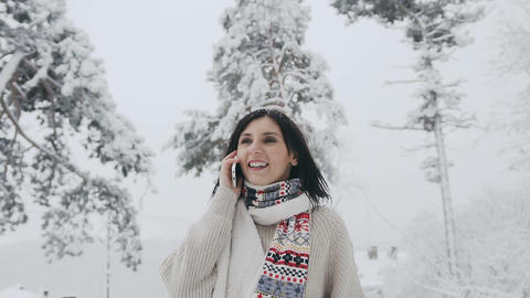 Asian young woman dressed in warm sweater and warm scarf talking on the her Live Action