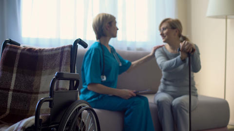 Nurse and aged woman sitting on sofa at hospital, discussing news, support Footage
