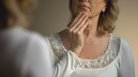 Mature female touching her wrinkled neck in front of mirror, aging process Footage