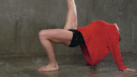 The dancer performs a dance piece on the floor under the spray of water rain Live Action