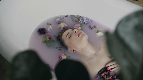 Attractive young woman in bath with milk and fragrant flowers of buds . Spa Live Action