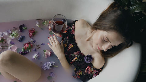 Sexy girl is relaxing in a warm milk bath with fragrant flower buds and drinking Live Action
