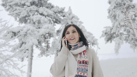 Asian young woman dressed in a warm sweater and warm scarf fun talking on the Footage