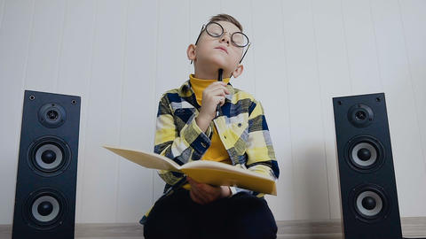 The blonde little boy in glasses with textbook sits on floor at home and records Live Action
