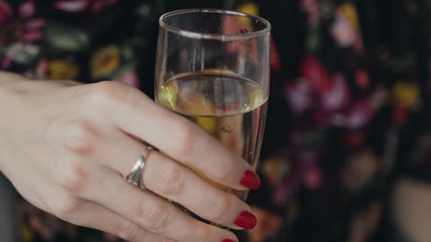 A glass of champagne in the young woman hand. The girl holds a glass of white Footage