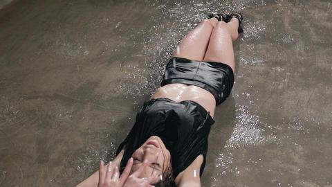Wet dancer in black sexy bodysuit is dancing on floor with studio light and Live Action