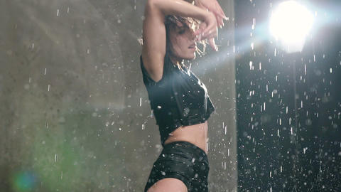 Wet girl performs contemporary dance under the water rain on the scene before Live Action