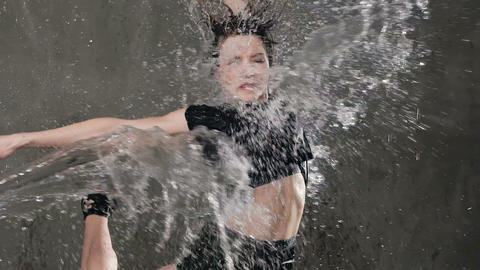 Beautiful dancer girl is performs a jump on the scene under the water rain with Live Action