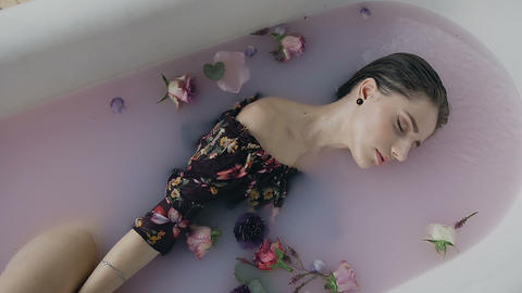 Cute girl in warm bath with milk and fragrant buds of flowers Live Action