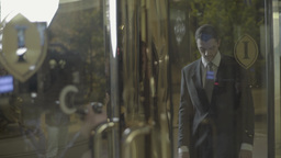 The cameraman shoots the actor in the revolving doors of the hotel Footage