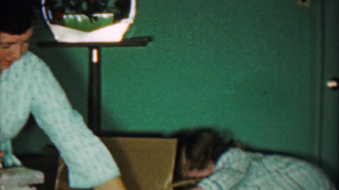 1958: Girl takes out 2 lamps from big box for Christmas gift Footage
