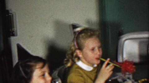 1958: Girl blows out birthday lamb animal cake candle party Footage