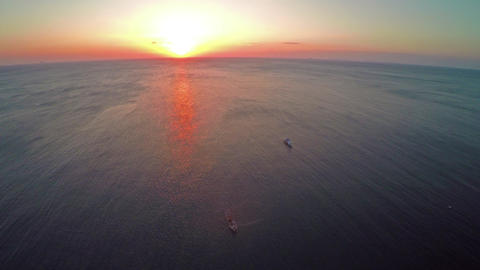 Flying over fishing boat in sea at sunset Footage