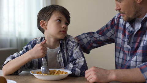 Little sad boy mixing cornflakes with spoon, looking at father, poor appetite Live Action