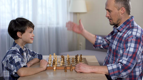 Male kid winning chess with his father, little son shaking hand with dad, hobby Live Action