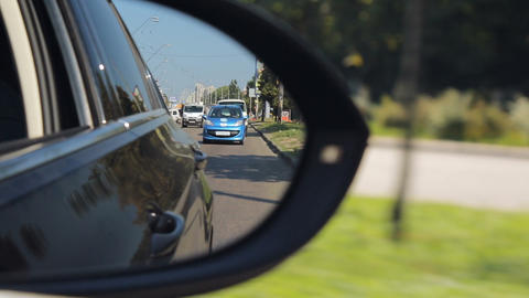 Reflection of city road in side rear view mirror, traffic rules, driving license Live Action