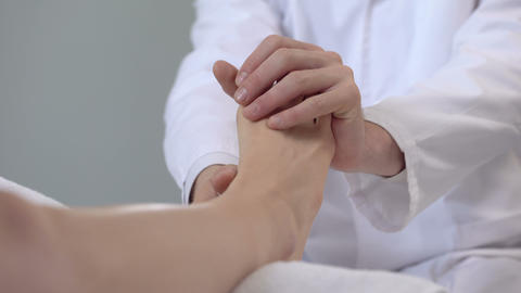 Physician examining patient sprained leg, first aid in trauma clinic, closeup Footage