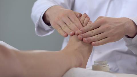 Specialist doing feet massage using cream, cosmetology procedures, beauty salon Footage